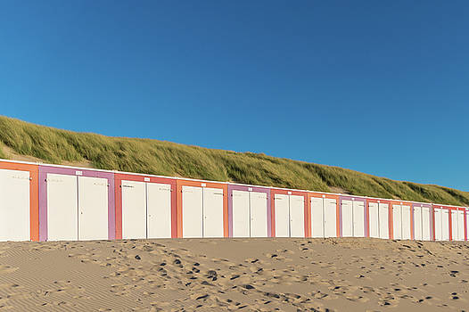 Colorful sheds at the beach in front of dunes during sunset by Maximilian Wollrab
