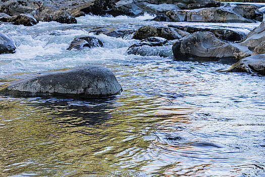 Colorful water reflections of sky and fall leaves in a rocky river by Natalie Schorr