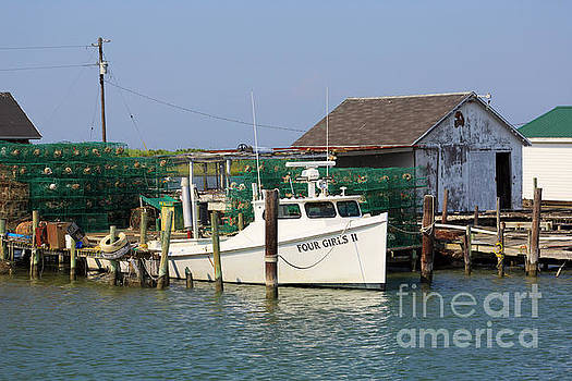 Crab pots beside a shanty and deadrise workboat on Tangier Island by Louise Heusinkveld