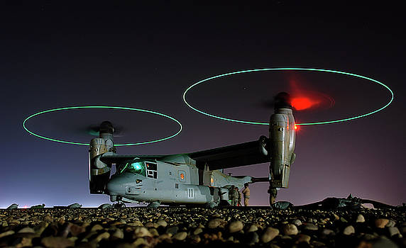 Crew members refuel an A V 22 Osprey before a night mission in central Iraq by Paul Fearn