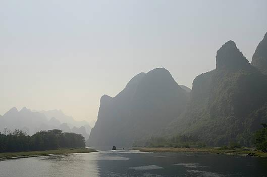 Reimar Gaertner - Cruise ship on the hazy Li River in China among the karst limest