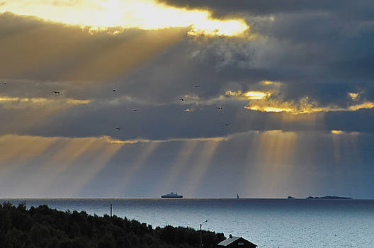 Cruise ship passing an island as sunrays shine through clouds by Intensivelight