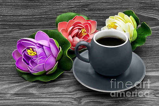 Cup of coffee and artificial colored water lilies by Nika Lerman