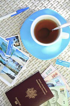 Cup of tea on a white table with postcards, money and passport by Virginie Blanquart