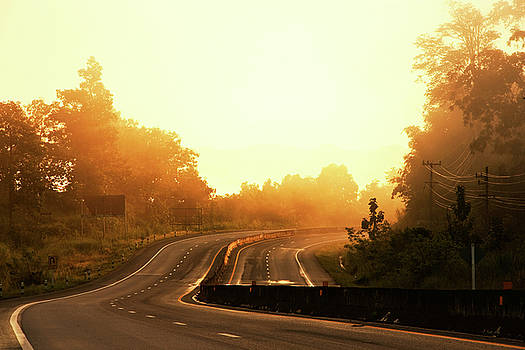 Curve road in morning sunshine by Akarapong Suppasarn