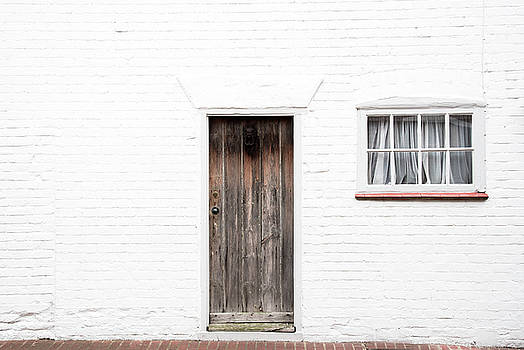 Door and window on a white wall by Michalakis Ppalis
