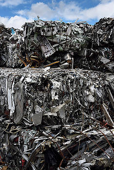 Reimar Gaertner - Dump with bales of crushed recycled scrap metal and blue sky clo