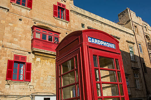 Red telephone cabin in the old town of Valleta by Julian Popov