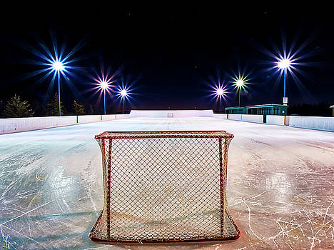 Empty outdoor rink at night by Darcy Michaelchuk
