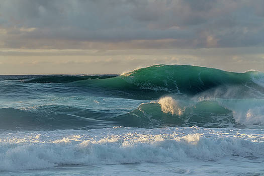 Evening light on large building waves at Ke'e Beach. by Larry Geddis
