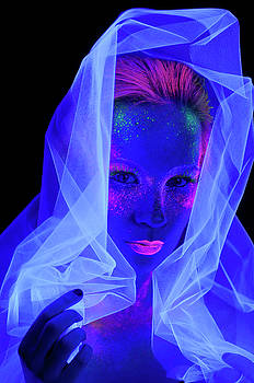 Reimar Gaertner - Face of woman in the dark with fluorescent paint makeup holding