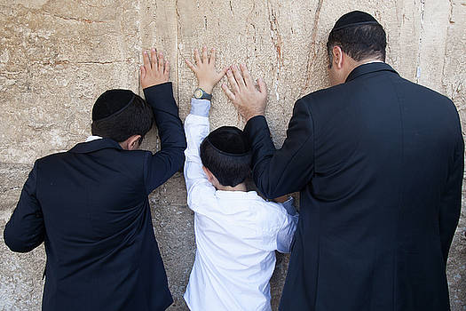 Father and son pray to G-d at the wailing wall by Yoel Koskas