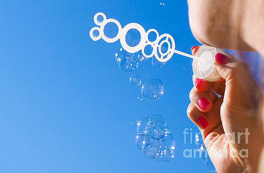 Female person blowing soap bubbles into blue sky by Arve Bettum