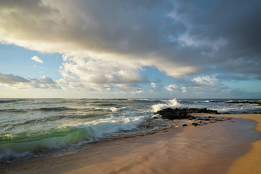 First light warmth at Poipu Beach along the South Shore. by Larry Geddis