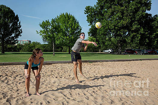 Herronstock Prints - Fit attractive male athlete blocks the serve during a volleyball match at Zilker Park
