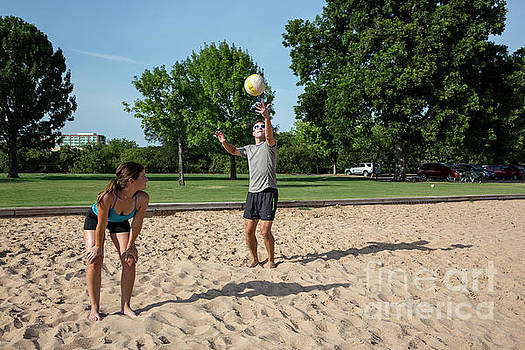 Herronstock Prints - Fit attractive male athlete serves the ball during a volleyball match at Zilker Park