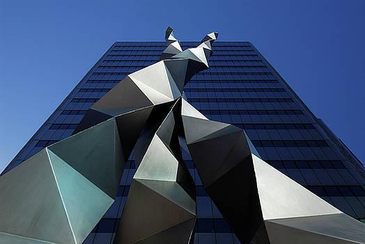 Reimar Gaertner - Folded triangular metal sculpture against a blue building and sk