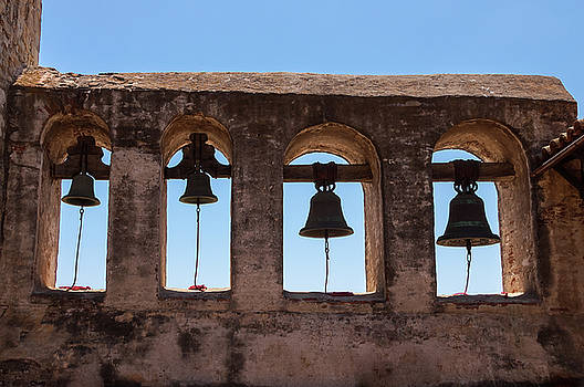 Four stationary bells hang from on an old Mission ruin by Bradley Hebdon