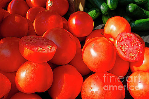 Fresh ripe tomatoes for sale in a farmers market by Louise Heusinkveld