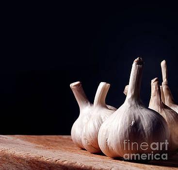 Garlic bulbs on wooden table by Jelena Jovanovic