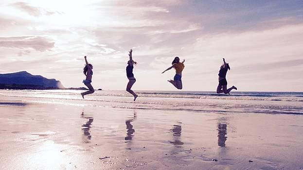 Girls jumping on Lofoten beach by Tamara Sushko