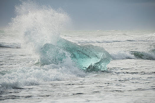 Glacial Iceberg in Beach Surf. by Andy Astbury