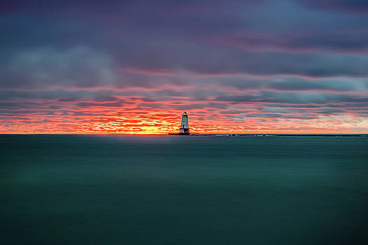 Glowing Sunset on Lake With Lighthouse by Lester Plank