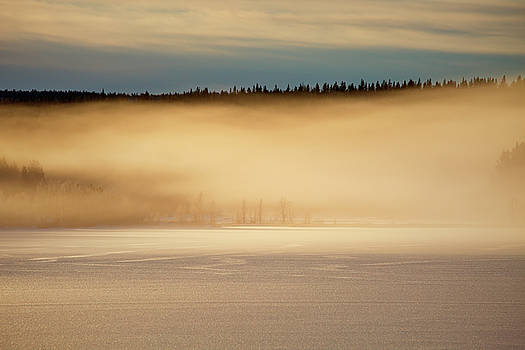 Golden mists are rising from an ice covered lake at sunset by Ulrich Kunst And Bettina Scheidulin