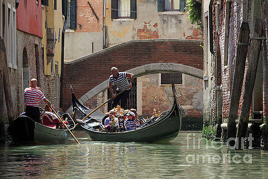 Gondoliers meet near a bridge on a canal in Venice Italy by Louise Heusinkveld