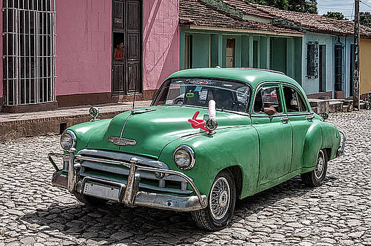 Green vintage vehicle on the colorful streets of Trinidad, Cuba. by Daniela Constantinescu