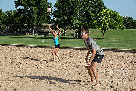 Herronstock Prints - Group of friends playing volleyball on the Zilker Park sand volleyball courts female returning the serve ball in play