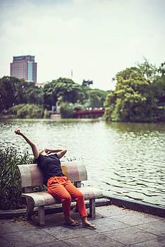HA NOI, VIET NAM,  Woman relaxing near the lake by Eduardo Huelin