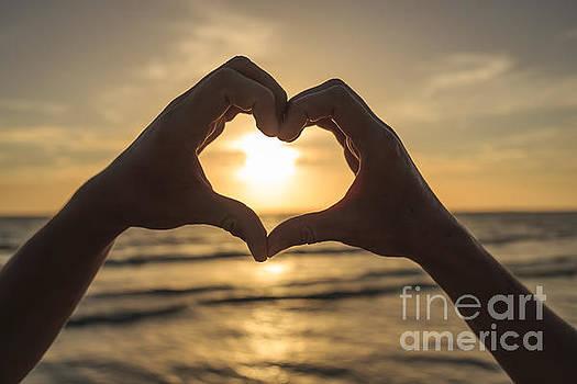 Edward Fielding - Hands forming heart around sunset