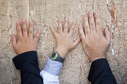 Hands of dad and son on The Wailing Wall, Jerusalem by Yoel Koskas