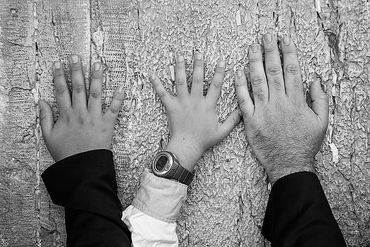 Hands of dad and son on The Wailing Wall  by Yoel Koskas