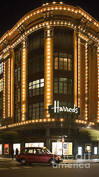 Harrods department store. Taxi passes in front of it by Deyan Georgiev