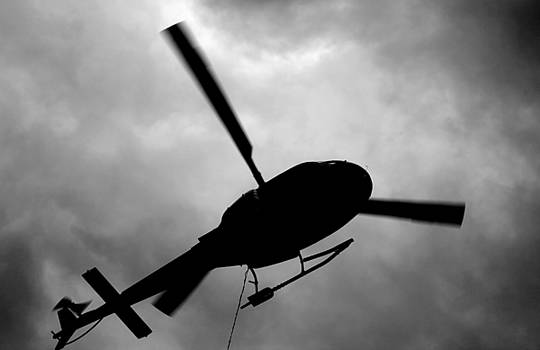 Helicopter Silhouette Hovering by Wyatt Rivard