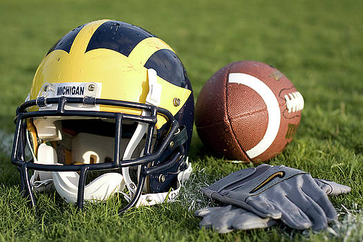 Helmet on the Field with Football and Gloves by Michigan Helmet
