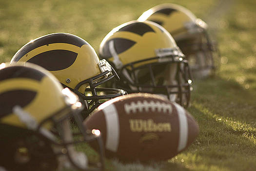 Helmets and a Football on the Field at Dawn by Michigan Helmet
