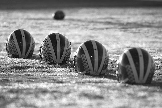 Helmets on Dew-Covered Field at Dawn Black and White by Michigan Helmet