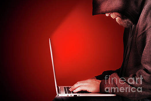 Hooded computer hacker red background by Simon Bratt Photography LRPS