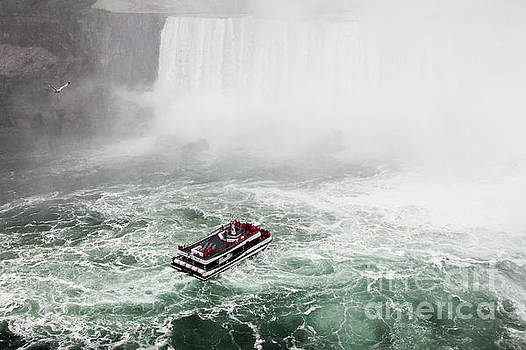 Hornblower boat with tourist on way to Niagara waterfall. by Miro Vrlik
