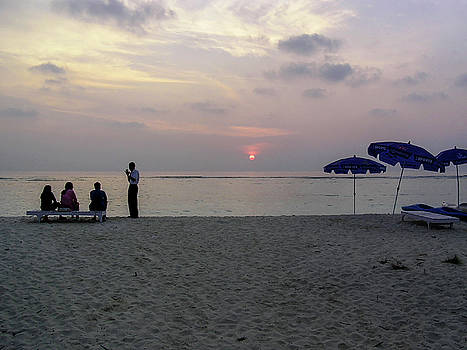 Host gesturing to a tourist family at sunrise in the Lakshadweep by Ashish Agarwal