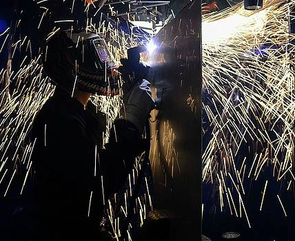 Hull Maintenance Technician Fireman cuts a piece of stainless steel   by Paul Fearn