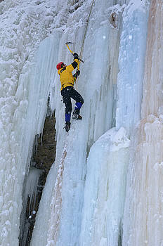 Reimar Gaertner - Ice climber swinging axe while front pointing up a steep icefall