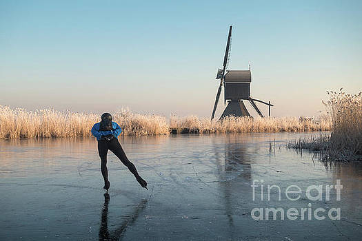 Ice skating past frosted reeds and a windmill by IPics Photography