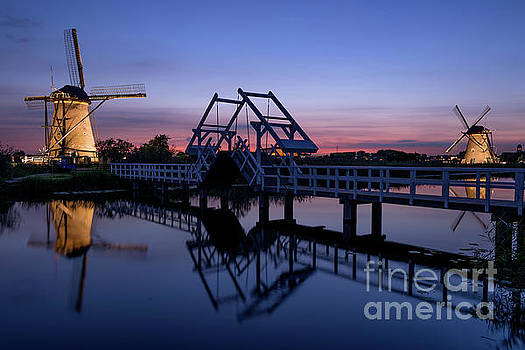 Illuminated windmills, a bridge and a canal at sunset by IPics Photography
