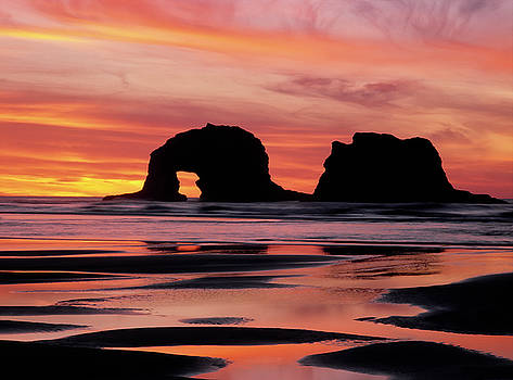 Incredible sunset colors silhouette offshore Twin Rocks and Rockaway Beach. by Larry Geddis