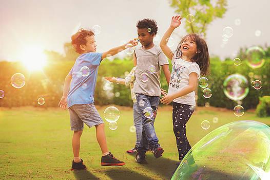 Kid and friends in international pre school play a bubble in pla by Anek Suwannaphoom