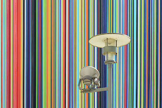 Lamp post against colorful wall by Virginie Blanquart